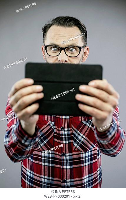 Man with eyes wide open looking excited at digital tablet