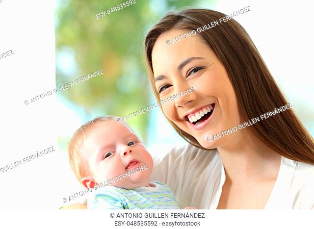 Front view portrait of a happy mother and her baby looking at you