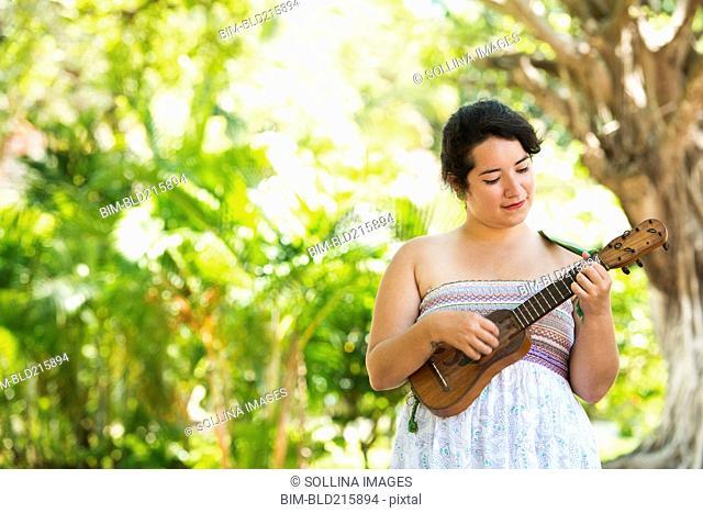 Hispanic musician playing ukulele in park