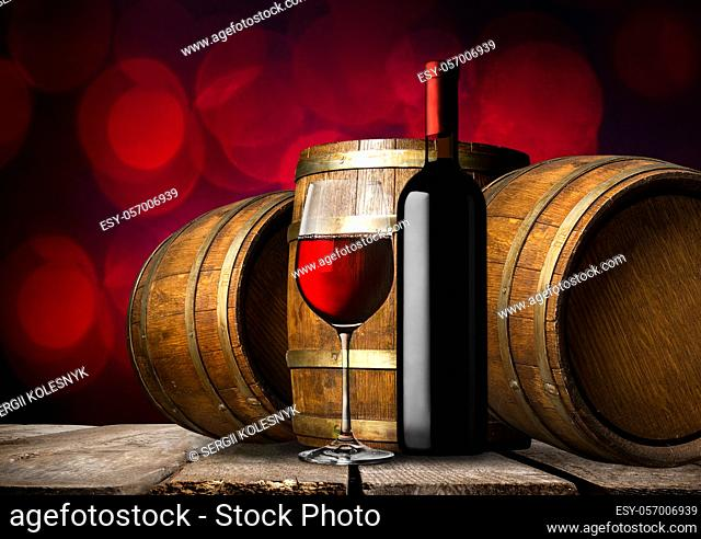 Bottle of red wine and wooden barrels