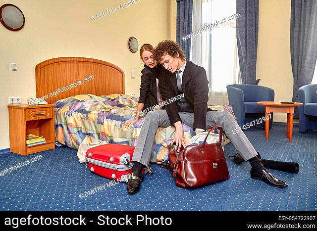 Happy young family with suitcases sits in the bed. Vacation