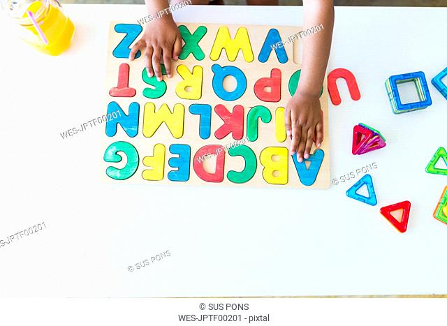 Close-up of girl playing with alphabet learning game on table