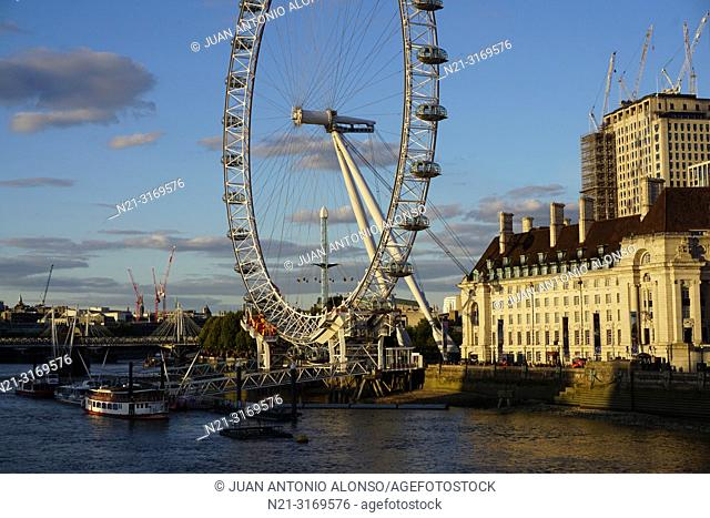 The London Eye and the County Hall on Queen's Walk. On the left, a view of the Hungerford and the Golden Jubilee bridges over the river Thames