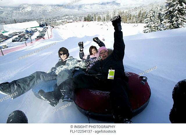 Family fun at the Blackcomb Mountain tube park; Whistler, British Columbia, Canada