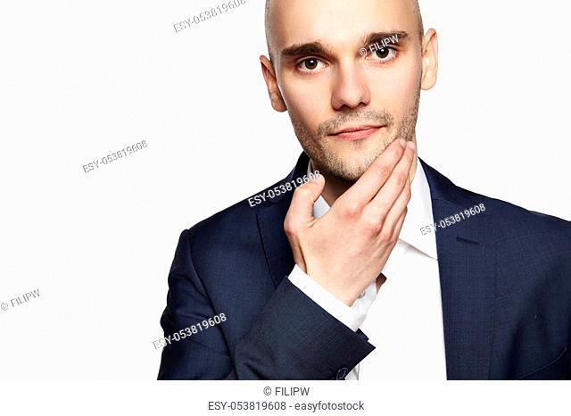 Portrait of a young man stroking his chin. Headshot on white background