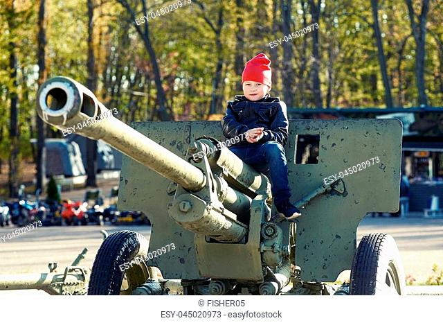 a boy plays in the Museum of military equipment