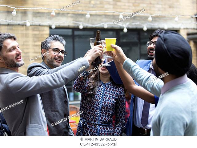 Friends toasting beer and cocktails at party on patio