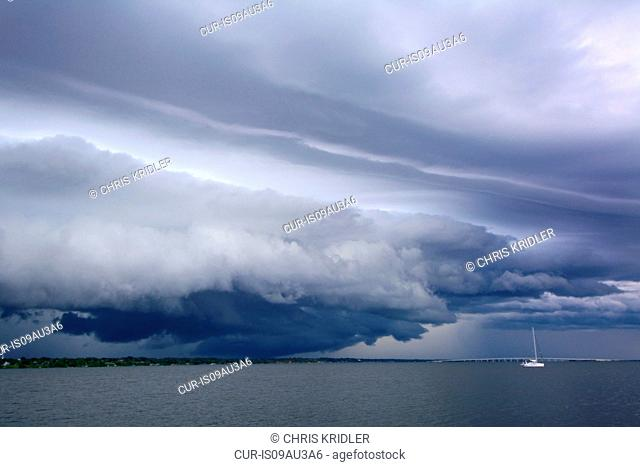 Arcus cloud over ocean and distant sailboat, Indian River lagoon, Cocoa, Florida, USA