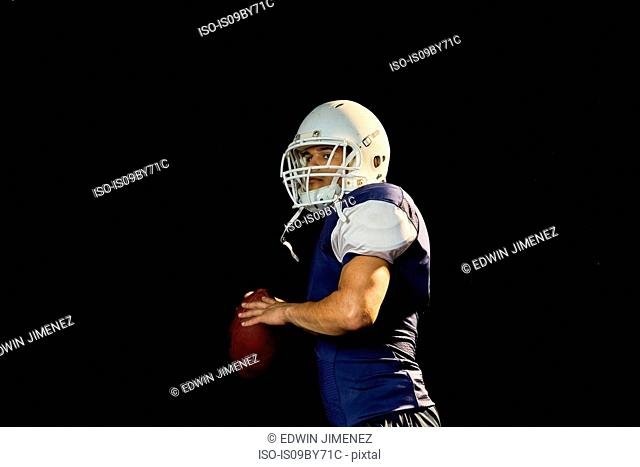Portrait of quarterback with football, black background