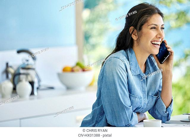 Smiling woman talking on cell phone in kitchen