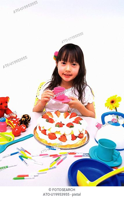 Little Girl holding a saucer and a cup, sitting at a table with a birthday cake and some kitchenware, looking at camera, Smiling, High Angle View