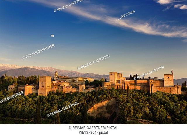 Moon and golden sunset on hilltop Alhambra Palace fortress complex Granada