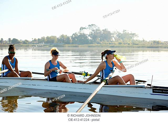 Female rowing team resting, drinking water in scull on sunny lake