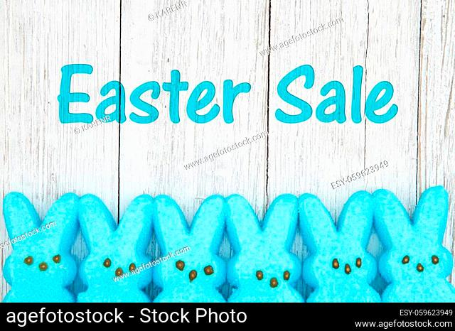 Easter sale message with blue candy bunnies on weathered whitewash wood