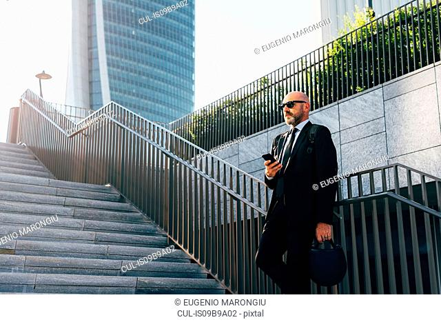 Mature businessman standing on steps, using smartphone, low angle view