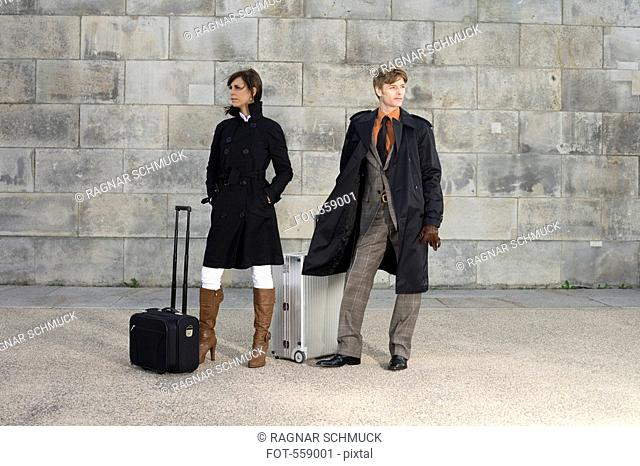 A man and woman waiting with luggage