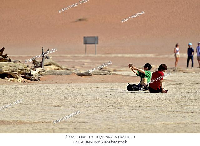 Asian tourists on the ground of Dead Vlei make selfies, taken on 01.03.2019. The Dead Vlei is a dry, surrounded by tall dune clay pan with numerous dead acacia...