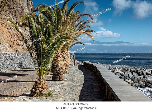A way close to the harbour in San Sebastian de la Gomera with palm trees, view to Tenerife