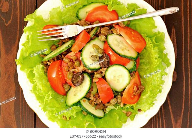 Lentil salad with tomatoes, cucumbers, capers and lettuce with thin fork on wooden table top view horizontal closeup