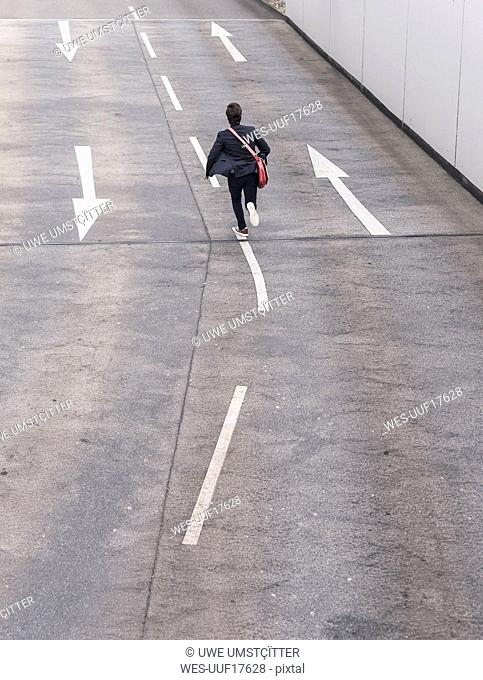 Rear view of businessman running on road with arrow signs