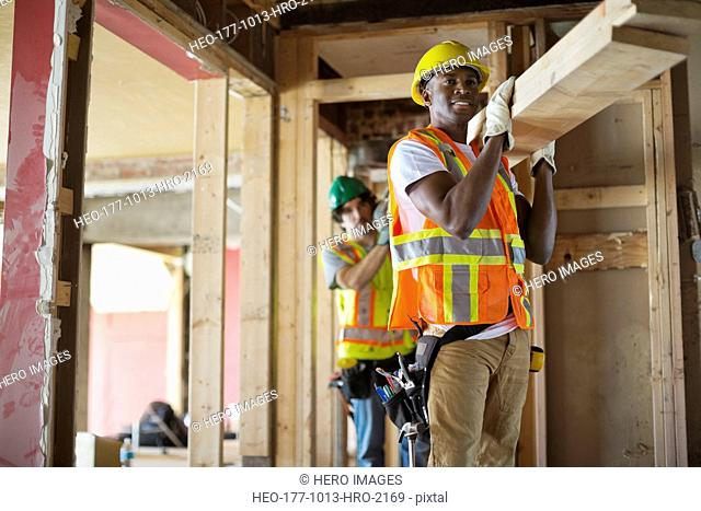 Tradesmen carrying lumber at construction site