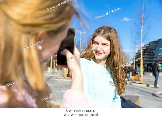 Russia, Moscow, teenage girls taking pictures of each other in the city