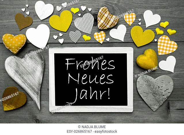 Chalkboard With German Text Frohes Neues Jahr Means Happy New Year. Many Yellow Textile Hearts. Grey Wooden Background With Vintage, Rustic Or Retro Style