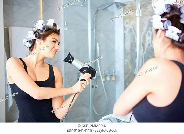 young woman putting curlers in her hair, bathroom
