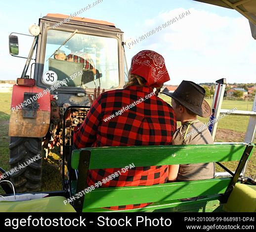 01 October 2020, Saxony, Wermsdorf: Cora Lechner drives with her life partner Johannes Boos and her children by tractor to the bison enclosure