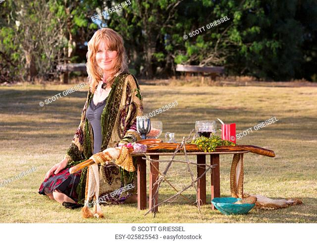 Beautiful female witch sitting on ground with altar