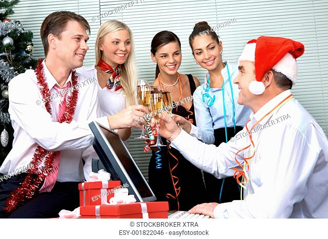 Image of cheering associates making toast with ceo in Santa cap at corporate party