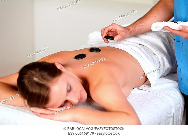 Close up of a woman relaxing while having a hot stone massage at a health spa resort