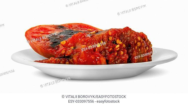 Rotting tomato on white plate isolated on white background