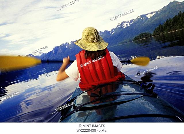 A woman sea kayaking on the flat calm water of Muir Inlet in Glacier Bay National Park