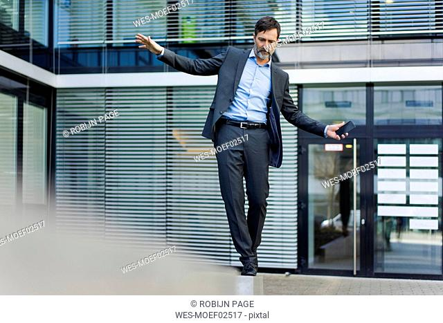 Mature businessman balancing on a wall outside office building