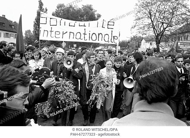 Daniel Cohn-Bendit (centre right, left of him a woman with flowers and to his right a man with megaphone) and students march towards the border checkpoint...