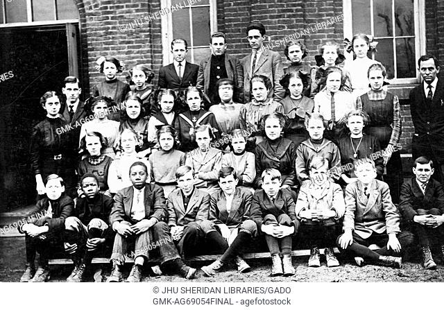 Full length landscape shot of schoolchildren, seated and standing outside building, some African American, one teacher, Ohio, 1920
