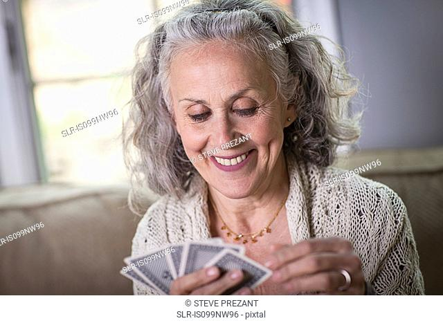 Senior woman playing card game at home