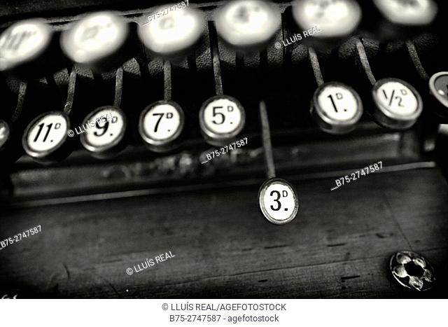 Close up of the keyboard of an old cash register machine, with different numbers