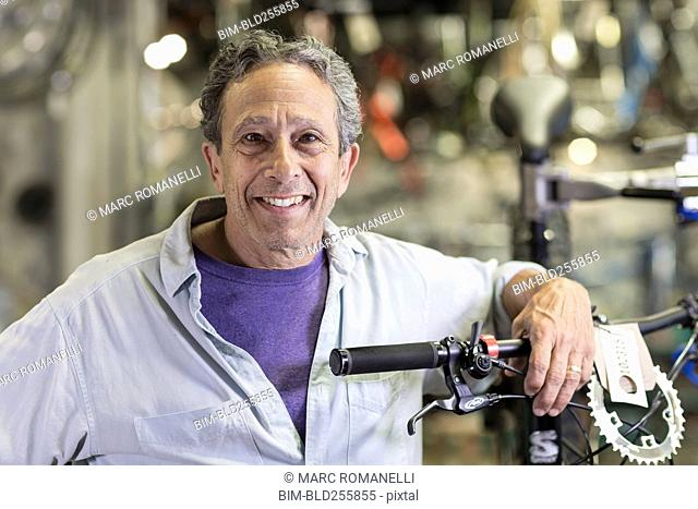 Portrait of smiling Caucasian man leaning on bicycle in shop