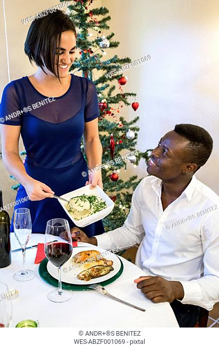 Woman serving mashed potatoes at Christmas dinner