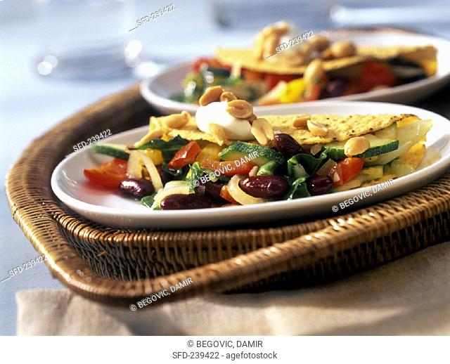 Taco shells with vegetable filling, soft cheese & peanuts