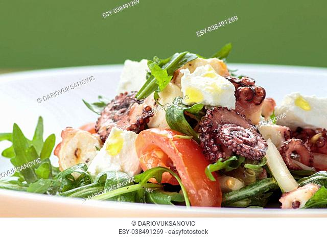 Octopus salad with rucola, olives and feta cheese on white plate with green background