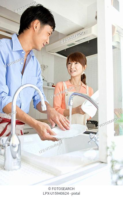 Young couple washing dishes
