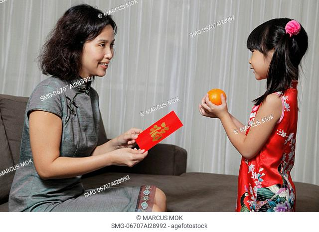Mother giving daughter a red envelopeHong Bao while daughter gives two oranges