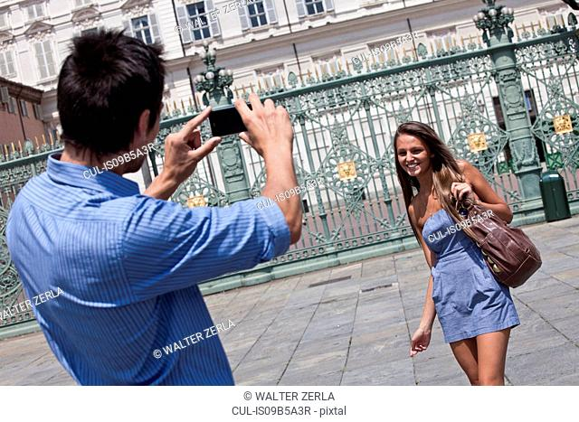 Young man taking photograph of young woman, using smartphone, Turin, Piedmont, Italy