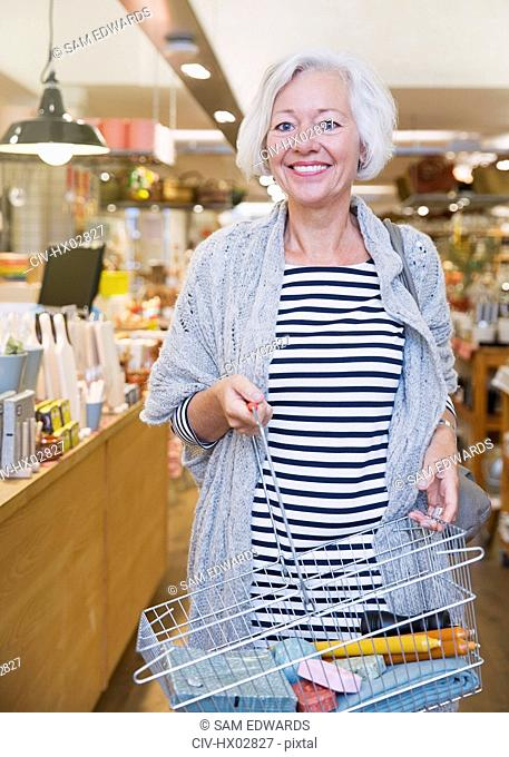Portrait smiling female shopper with basket in shop