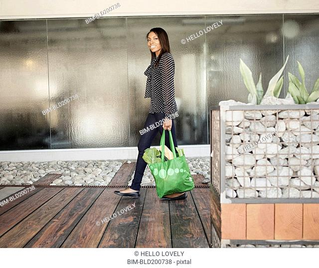 Woman carrying bag of groceries
