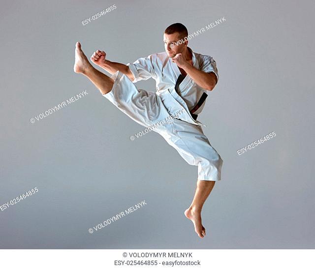 Man in white kimono and black belt training karate over gray background
