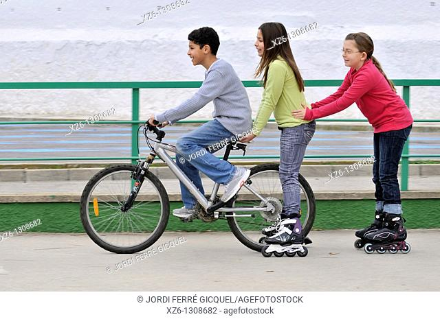 Group of children with bicycle and in-line skates. Spain